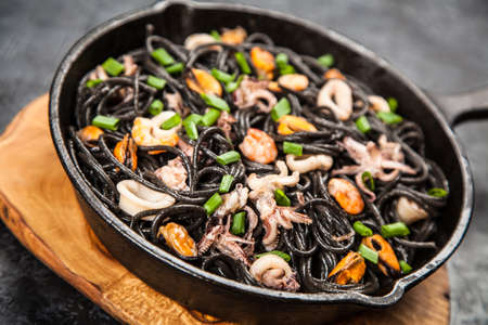 Black spaghetti made of squid ink with shrimps and other seafood