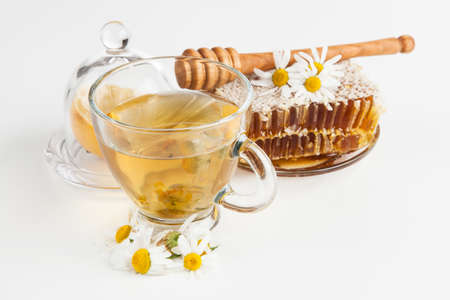 Honeycomb and chamomile tea on white Stock Photo