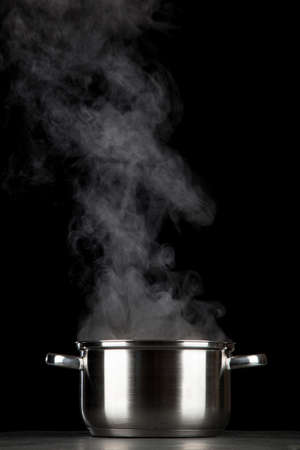 Steaming pot on black background 写真素材