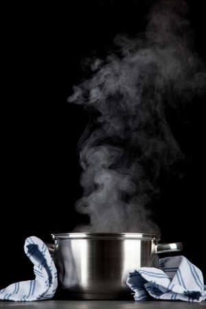 Steaming pot on black background Archivio Fotografico