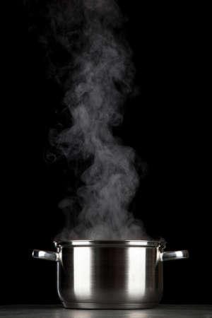 Steaming pot on black background Banque d'images