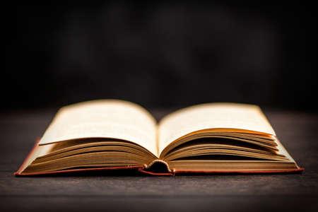 Open book on dark background Foto de archivo