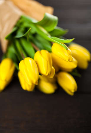 Yellow tulips on wooden background Stock Photo
