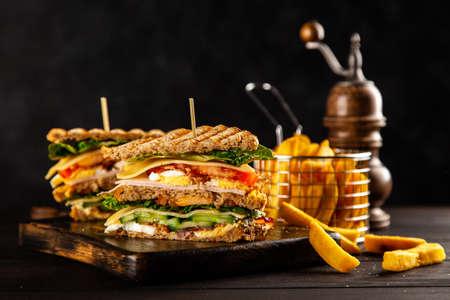 Sándwich club alto y papas fritas Foto de archivo