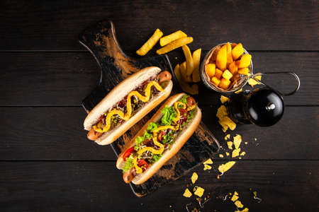 Three delicious hotdogs on dark wood background Stok Fotoğraf