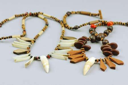 godliness: Sundry indian necklace with wooden and crocodilian tooth on white background Stock Photo