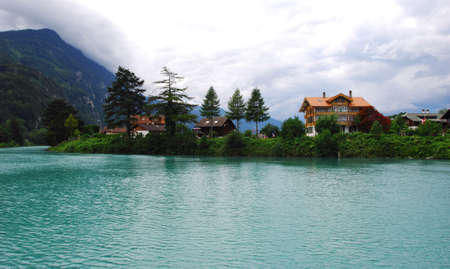 A view of the thorp beside river, with mountains and cloudy sky. Interlaken, switzerland