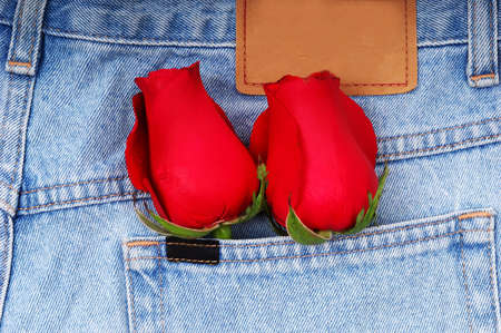 A couple of roses in a denim pocket. photo