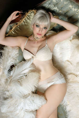 Beautiful Woman with feathers relaxing on couch in lingerie Banco de Imagens - 2576290