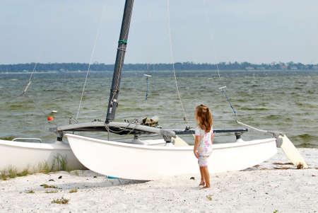 Young child looking at catamaran