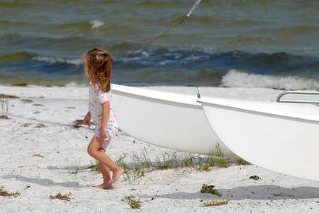 Little girl walking awy from catamaran