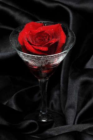 Red rose and glass on black satin  Banco de Imagens