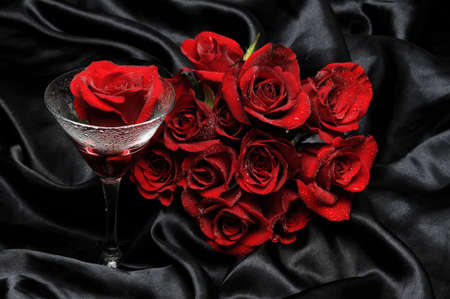 Red roses and glass on black satin