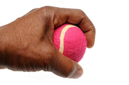 Hand gripping pink tennis ball