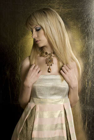Beautiful blonde woman in gold colored dress