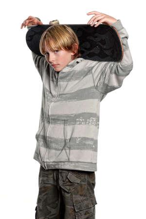 Young teenage boy with skateboard behind head
