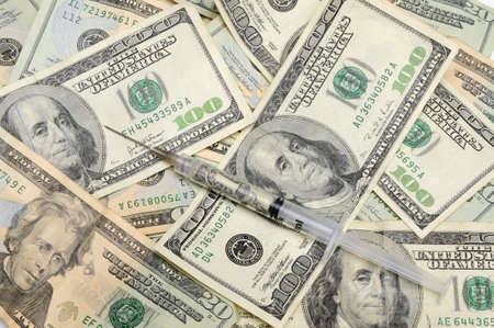 Syringe with money inside on money background Banco de Imagens