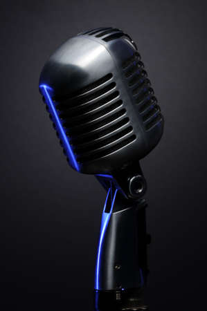 Vintage microphone on grey with blue highlights Banco de Imagens