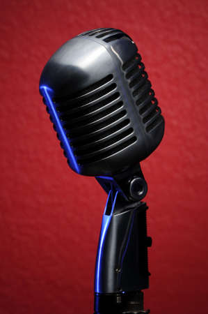 Vintage microphone with blue highlights on red background Banco de Imagens