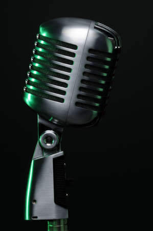 Vintage microphone with green highlights on dark background