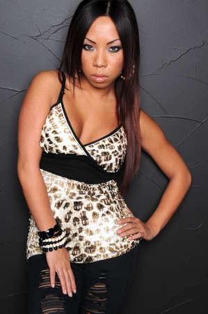 Beautiful Asian woman leaning on wall