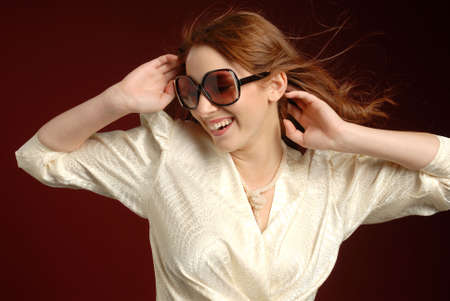 Fashionable smiling woman with red hair wearing sunglasses