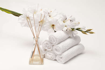 Aromatherapy spa diffuser with towels and flower on white