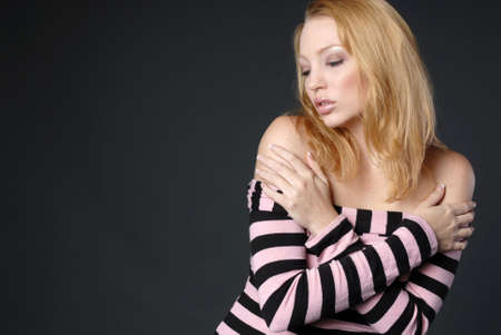 Beautiful blonde woman in black and pink top with hands on shoulders