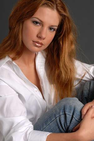 donne mature sexy: Bella donna con i capelli lunghi rossi in camicia bianca e jeans seduta