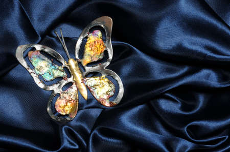 Metal colorful butterfly on blue satin fabric