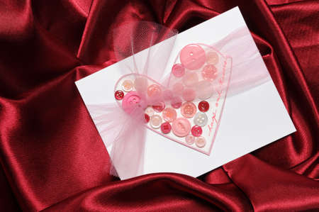 Handmade Valentines Day card using buttons on red satin background