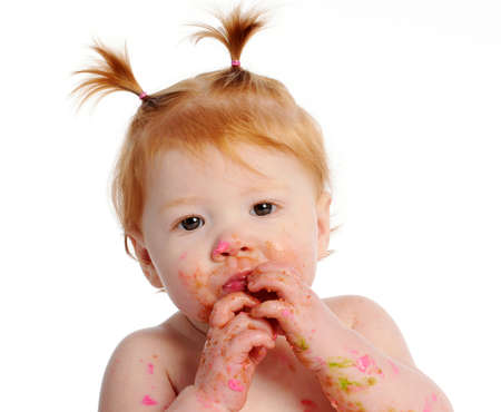 Messy baby with icing on face and hands Banco de Imagens - 9637343