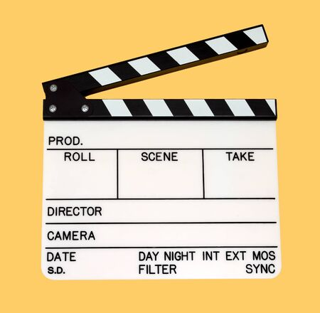 closeup of a movie clapper over yellow background