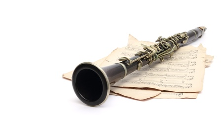 an old clarinet on music sheets over white Stock Photo