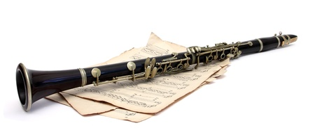 musical instrument parts: an old clarinet on music sheets over white Stock Photo