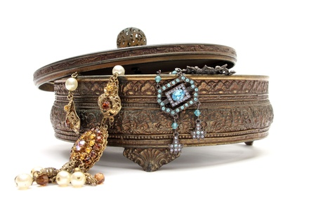 an old jewelery box with old jewels in it over a white background