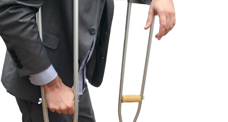 closeup of the body of a business man taking a break with his crutches