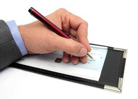 chequera: Primer plano de una mano escribiendo un cheque