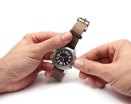 closeup of two hands changing the time on a watch Stock Photo