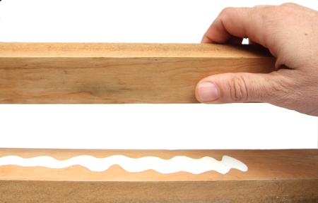 hand working on wood pieces with glue