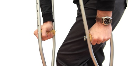 pierna rota: Primer plano de un hombre caminando con muletas sobre fondo blanco