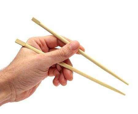 close-up van een hand met stokjes op een witte