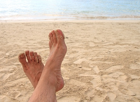 feet of a man relaxing on the beach