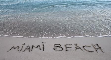 beach writing of miami beach with blue sea water