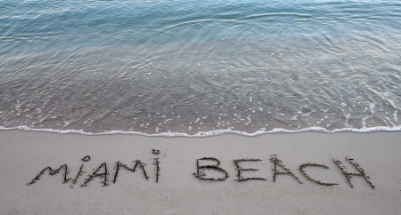 beach writing of miami beach with blue sea water