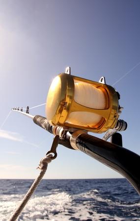 trolling: Ca�a de pescar con carrete de arrastre en un barco Foto de archivo