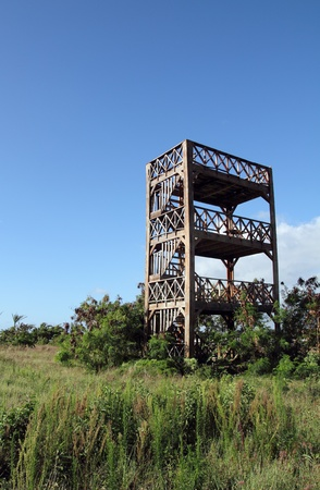image of a wood tower in a field with blue sky