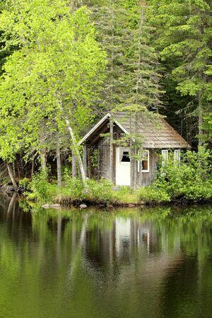 piccola casa di legno facendo una riflessione su un lago calmo Archivio Fotografico
