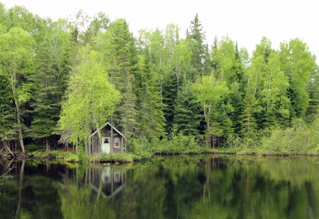 little wood house making a reflection on a calm lake Imagens