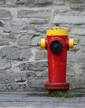 closeup of a red and yellow fire hydrant with a rock wall background photo